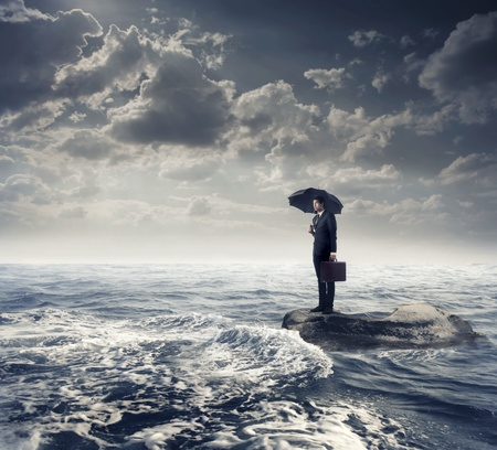 Businessman under an umbrella on a rock in the middle of a slight sea under stormy sky