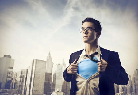 Foto de Businessman showing the superhero suit under his shirt with cityscape in the background - Imagen libre de derechos