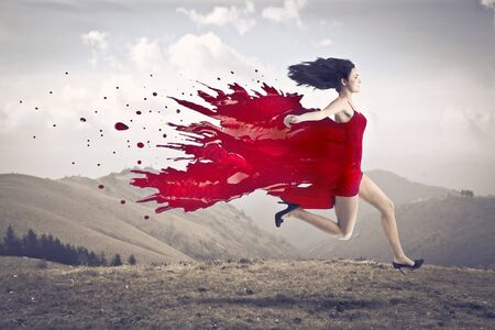 Beautiful woman running on a hill with her dress melting in red paint