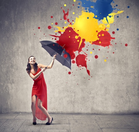 Photo for Laughing beautiful woman using an umbrella as a shelter against paint drops falling down - Royalty Free Image