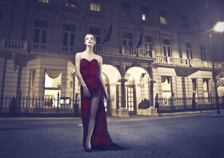 Beautiful woman wearing an evening gown with luxury building in the background