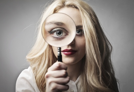 Beautiful woman holding a magnifying glass