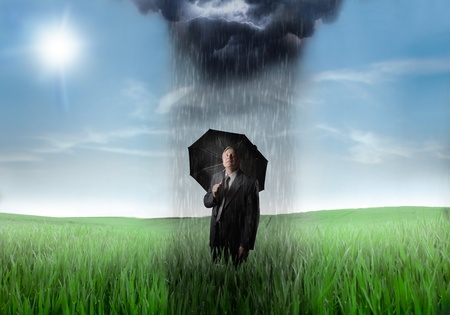 Sad senior businessman under an umbrella on a green meadow with raincloud over him and sunny sky in the background