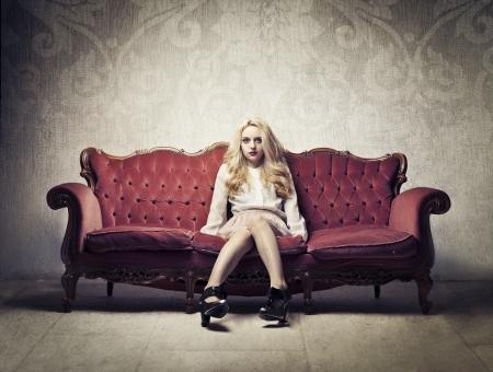 Beautiful rich woman sitting on a velvet sofa
