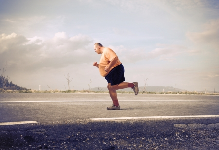 Overweight man jogging on a country road