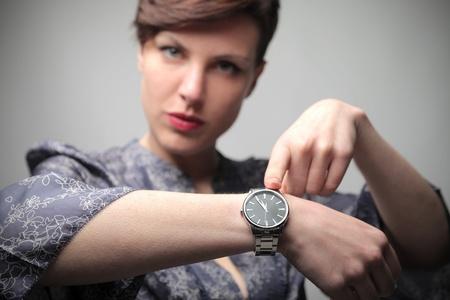 Photo pour Beautiful woman showing the time on her wristwatch - image libre de droit