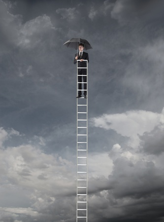 Young businessman on a ladder holding an umbrella with stormy sky in the background