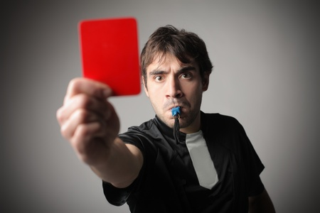 Angry referee whistling and raising a red card