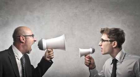 Businessman screaming into a megaphone against a younger businessman holding a smaller megaphone