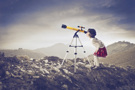 Little girl looking into a telescope on a hill