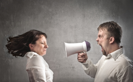 Angry man screaming into a megaphone against his girlfriend