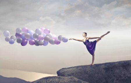 Blonde dancer stepping on a cliff holding some ballons