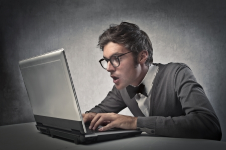 Fashionable man surprising while using a laptop computer