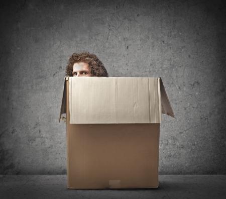 Man hiding behind a box
