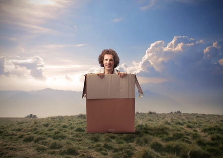 Man coming out from a box in a wasteland