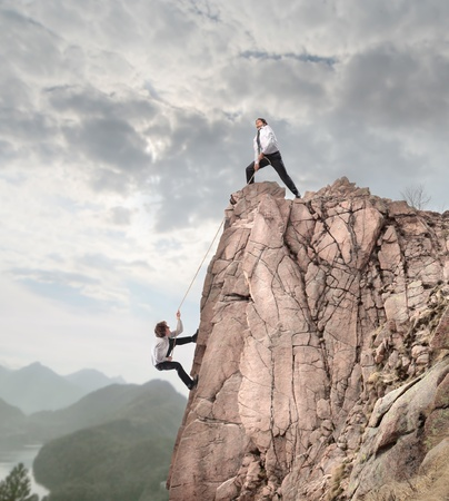Businessman on the top of a rock helping another businessman to climb it