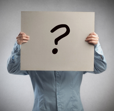 Man holding a cardboard on which is drawn a question mark