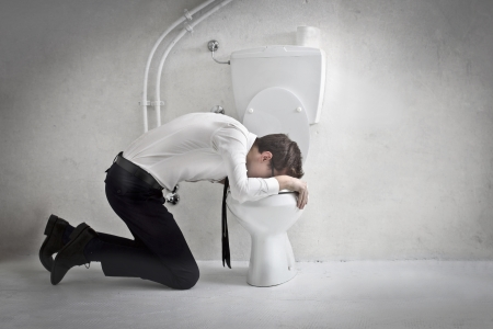 Young businessman puts his head in a toilet