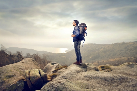 young man with backpack in the mountains