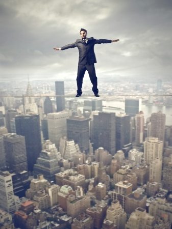 young businessman balancing on rope over the city