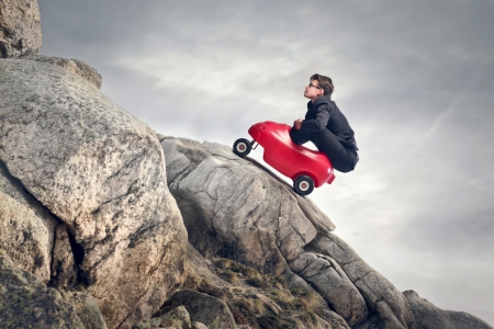 young businessman climbs mountain with small red car