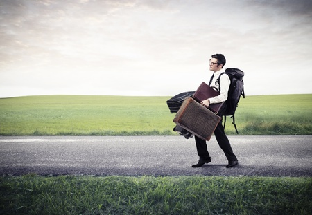 young businessman with many luggages on the road