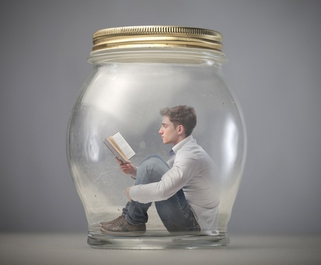 young boy reads book sitting in a jar