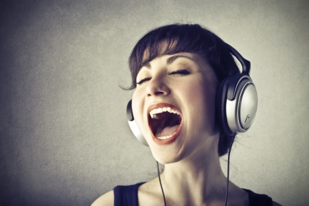 young woman with headphones singing