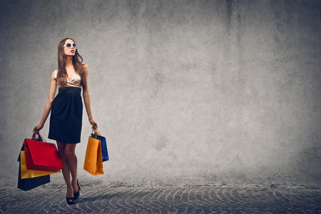 elegant woman goes shopping on gray background