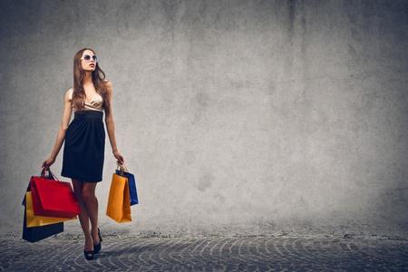 Foto de elegant woman goes shopping on gray background - Imagen libre de derechos