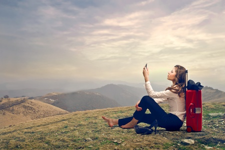 woman on the top of a mountain looking at her mobile