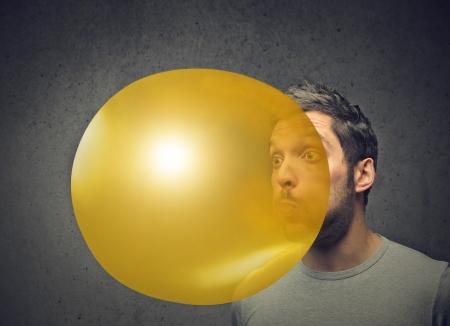 man blowing a yellow balloon