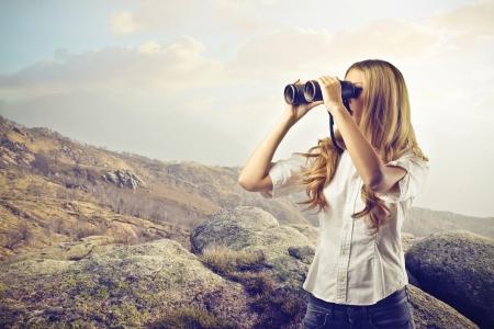 Foto de woman looking at something with a binoculars - Imagen libre de derechos