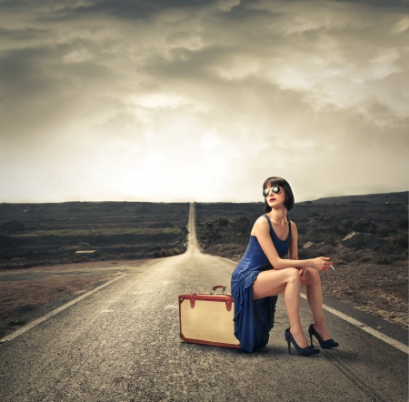 Fashion woman sitting on her luggage