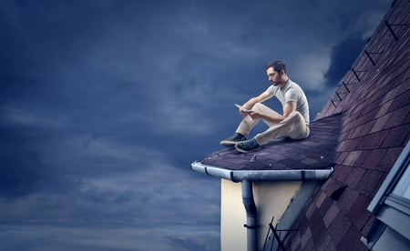 man on the roof of a house