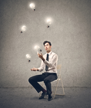 businessman playing with some light bulbs