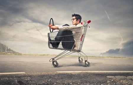 businessman into a cart pretending to drive a car