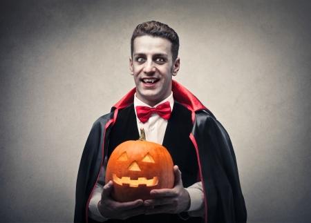 vampire holding a pumpkin