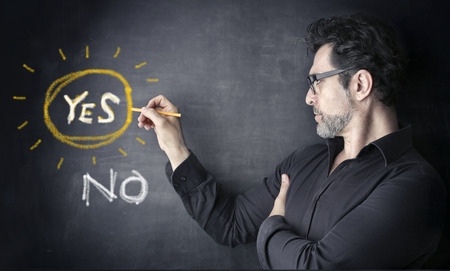 man with yes or no on a black board