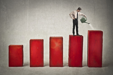 Businessman watering some statistics columns