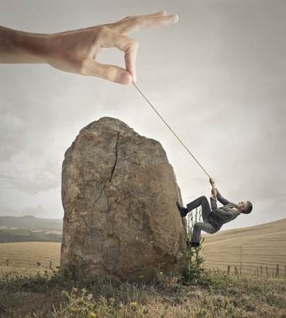 Businessman trying to climb a rock with the help of a giant hand