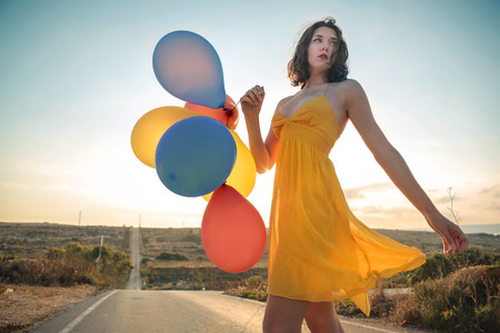 Foto per Girl holding colorful balloons - Immagine Royalty Free