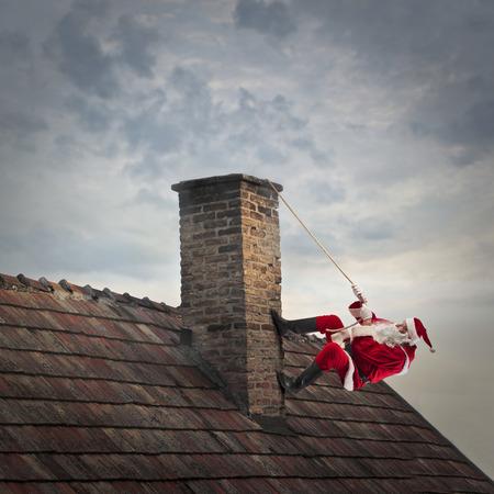 Santa Claus climbing on a chimney
