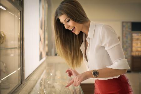 Photo pour Young woman choosing a jewel - image libre de droit