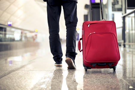 Photo pour Travelling with a red trolley - image libre de droit