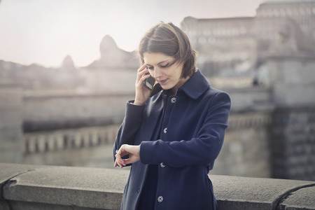 Photo pour Young Lady is checking her watch while she is speaking on her phone - image libre de droit