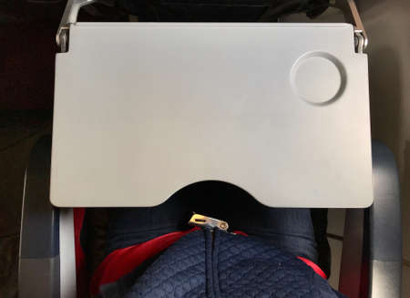 Foto de Passenger who wears blue jeans is fastening red seat belt in airplane cabin. There are tray table and seat belt for passenger in each chair on the plane. - Imagen libre de derechos