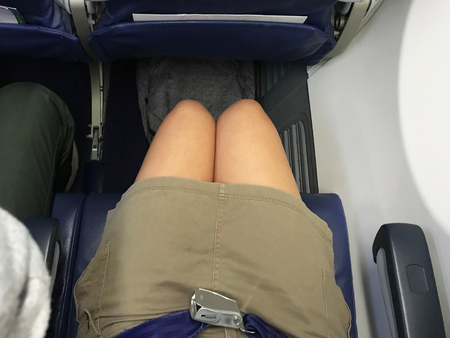 Passenger who wears brown short skirt jeans is fastening blue seat belt in airplane cabin. There are tray table and seat belt for passenger in each chair on the plane.