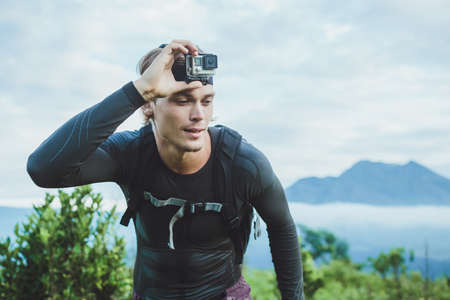 Photo pour Attractive Traveler vith  camera on his hand against the Batur volcano from Kintamani, Bali, Indonesia - image libre de droit