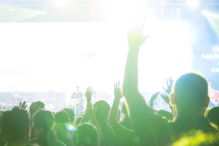 Photo for A crowd level view of hands raised from the spectating crowd interspersed by colorful spotlights and a smokey atmosphere - Royalty Free Image